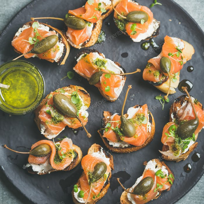 Homemade salmon crostini with cream-cheese, watercress, capers and pesto suace