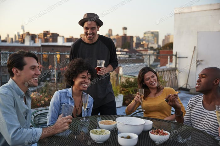 Six adult friends enjoying a party on a rooftop, close up
