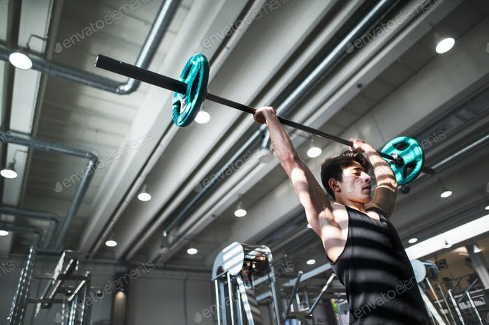 Fit young man in gym working out, lifting barbell. Copy space.