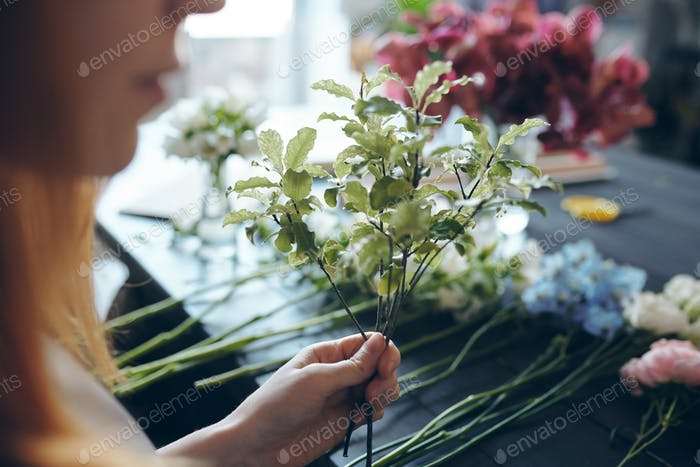 Adding greenery into bouquet for texture