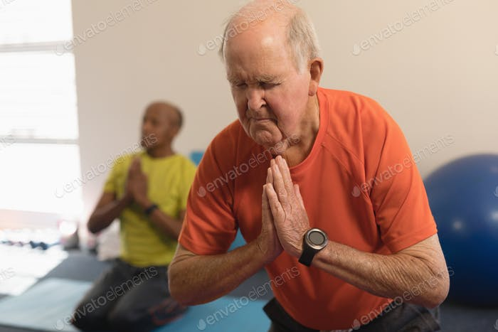 Front view of senior woman doing yoga on the foreground with his friend behind his in fitness studio