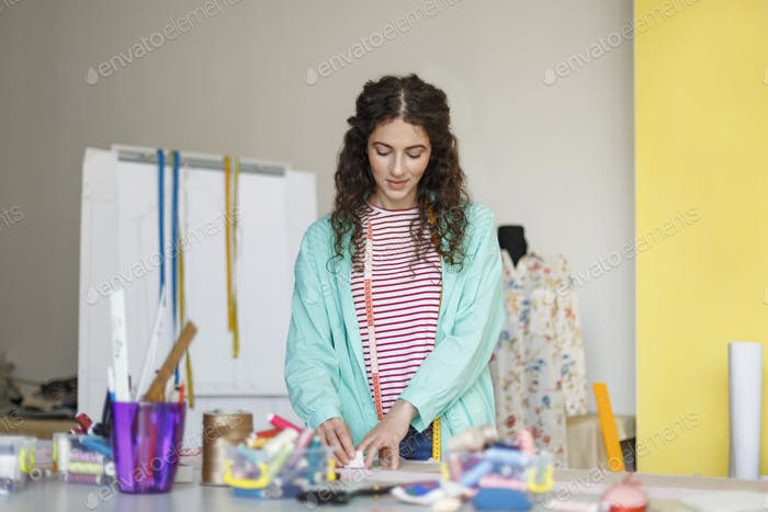 Young smiling tailor with measuring tape dreamily working in sew