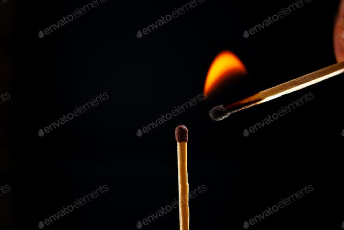 Side view of lighting one match to another one on dark background