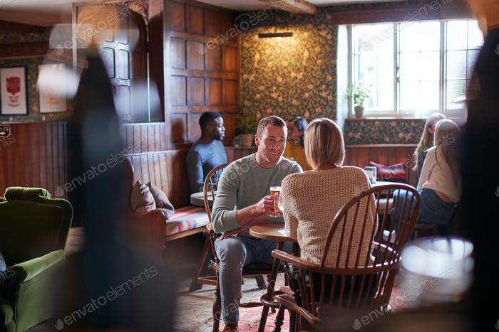 Couple Meeting For Lunchtime Drinks In Traditional English Pub Making A Toast