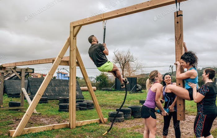 Participants in obstacle course doing pegboard and rope