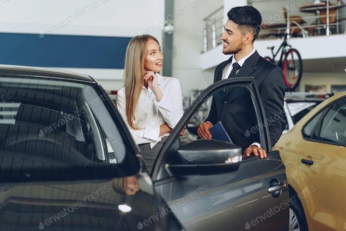 Man car dealer showing a woman buyer a new car