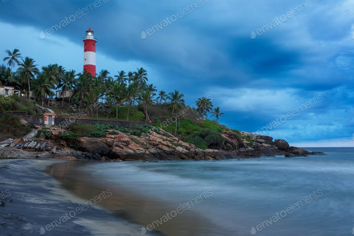 Gathering storm on beach and lighthouse on sunset. Kerala, India