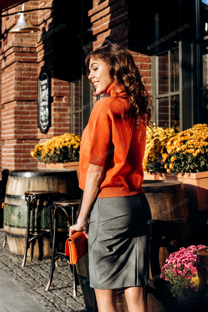 Stylish slim girl dressed in gray skirt, orange blouse holding orange little bag walks in the street