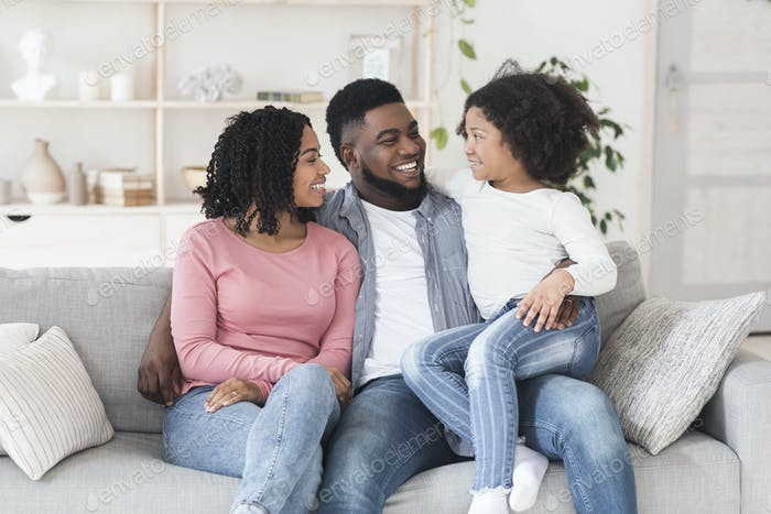 Happy African American Parents Bonding With Their Little Daughter At Home