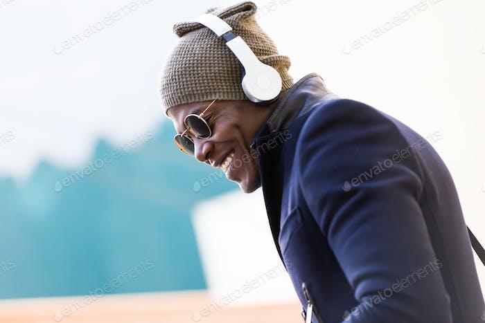 Joven guapo escuchando música en la calle.