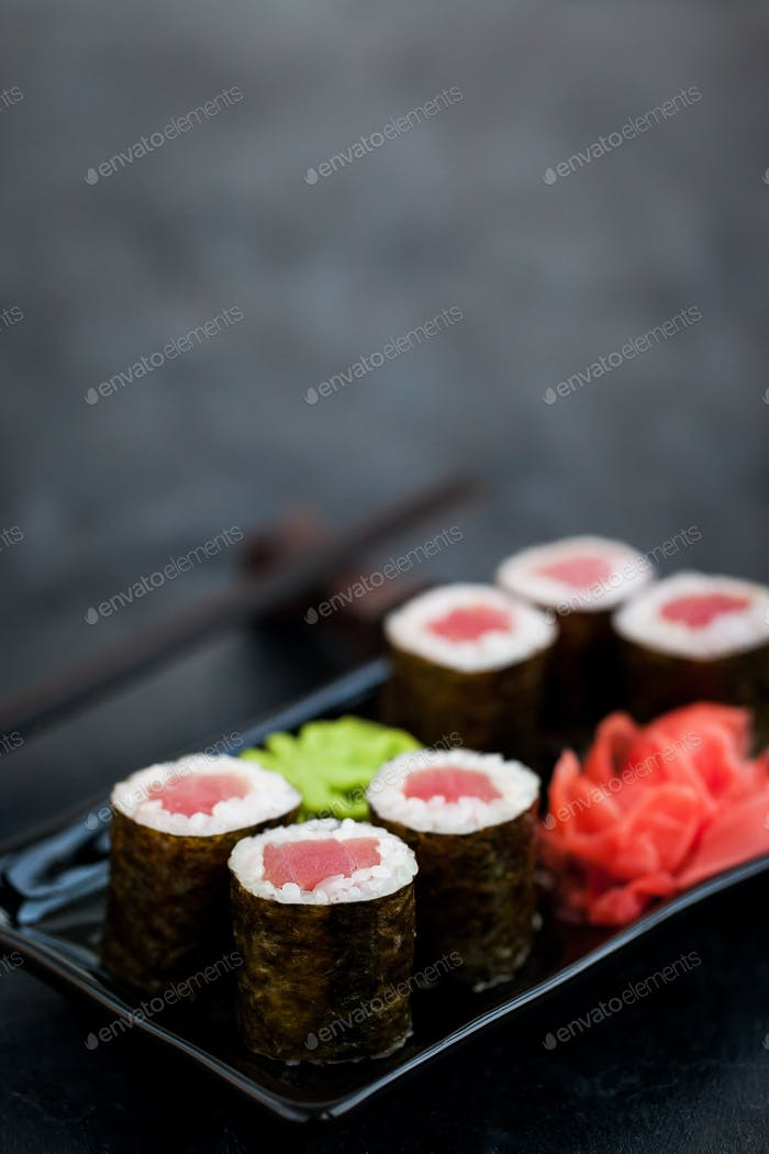 Fresh delicious tuna maki sushi rolls on dark background