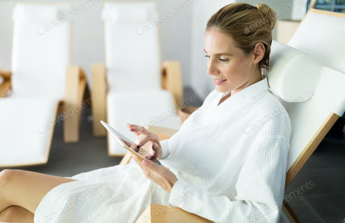 Beautiful woman relaxing and using tablet in spa
