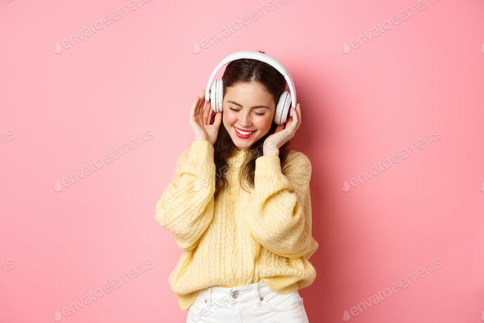 Portrait of attractive brunette girl enjoying listening music, dancing and smiling pleased, standing