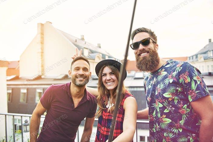 Frau und zwei männliche Freunde stehen auf der Terrasse