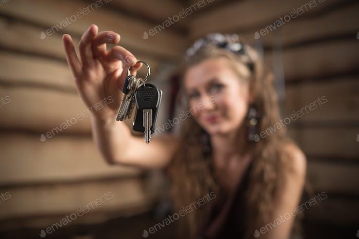 Beautiful smiling woman holds blurry keys