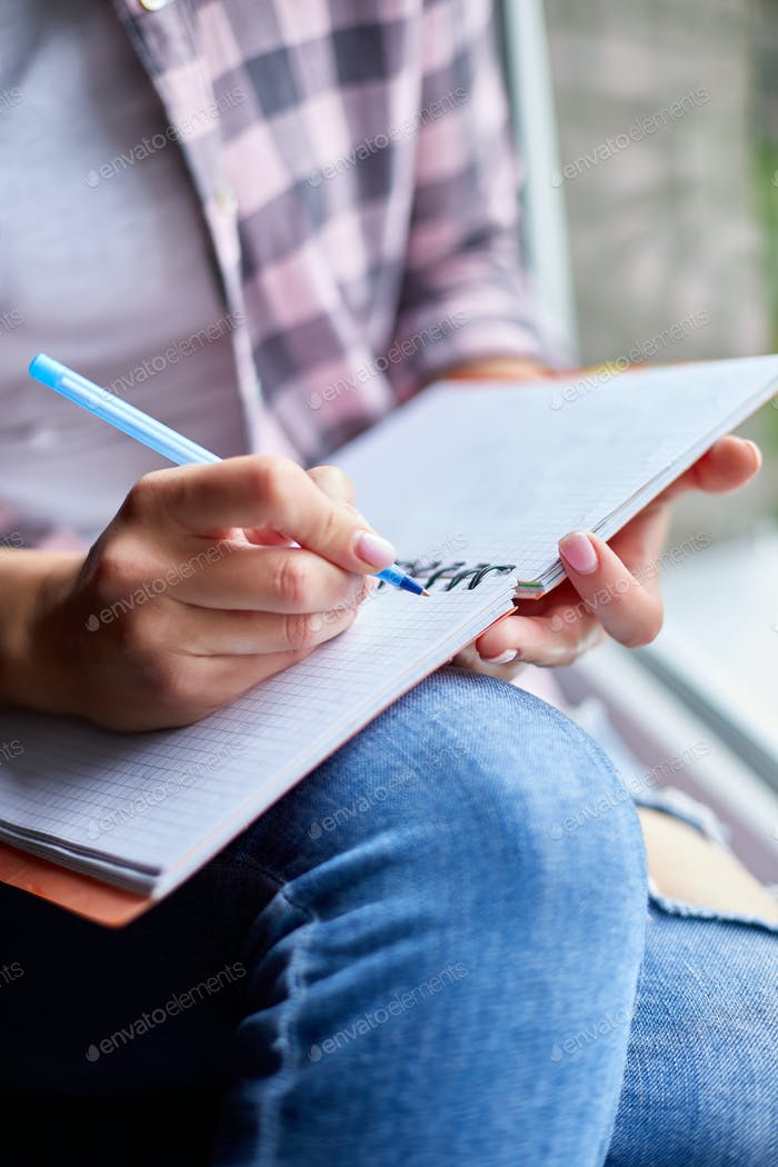Woman, sitting at window at home, writes in notebook goals