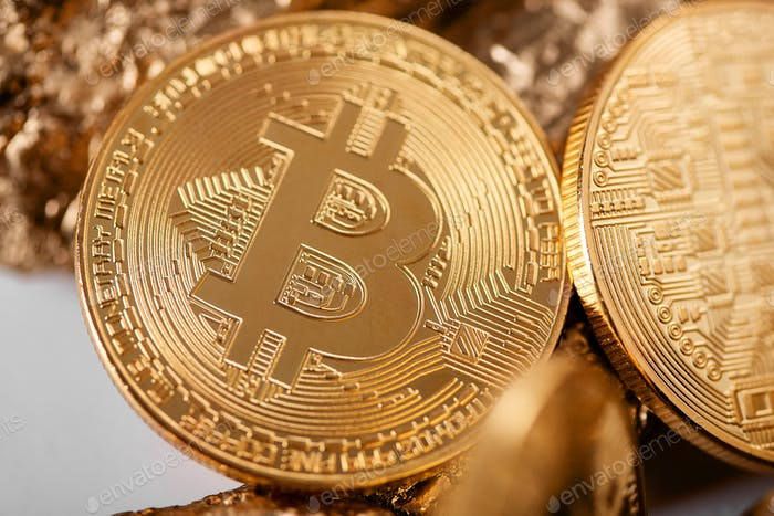 Closeup of golden bitcoin as main cryptocurrency with gold lumps being blurred on background