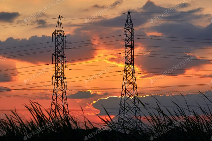Silhouetted electricity pylons with the vivid sky of sunset