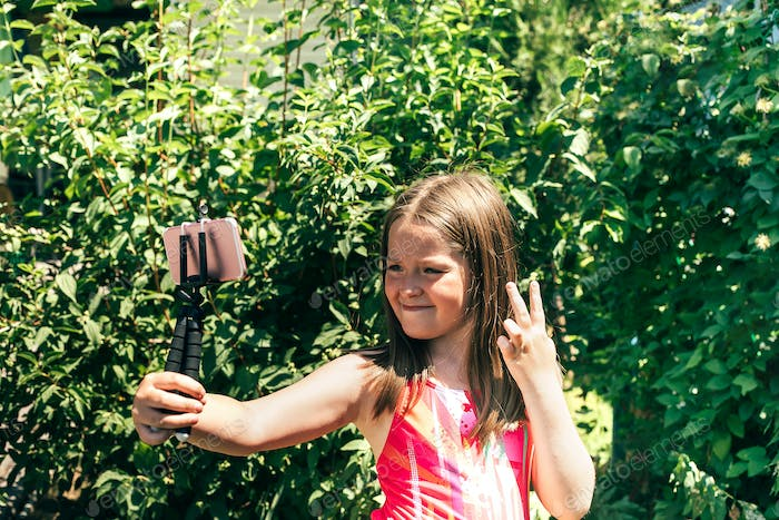 Smiling little girl 7-8 years old making selfie photo on smartphone over green background