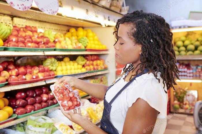 Woman buying fresh strawberries