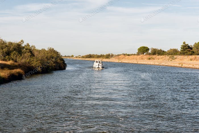 Boat cruising down a canal in the Camargue
