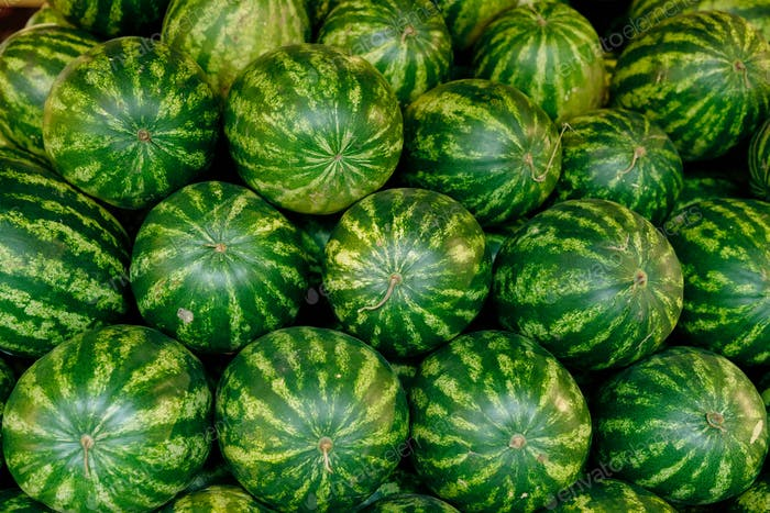 Pile of big ripe green watermelons in supermarket