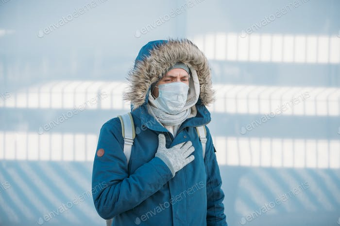 man having a cold, feeling unwell, wearing medical face mask, experiencing chest pain, outdoors