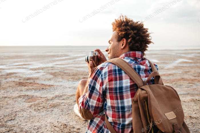 Back view of happy man taking pictures on the beach