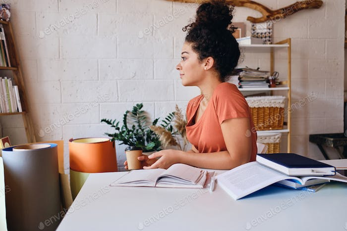 Student girl sitting at the desk with coffee and notebooks around dreamily looking aside studying