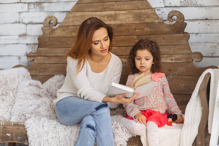 Beautiful mother and daughter reading book