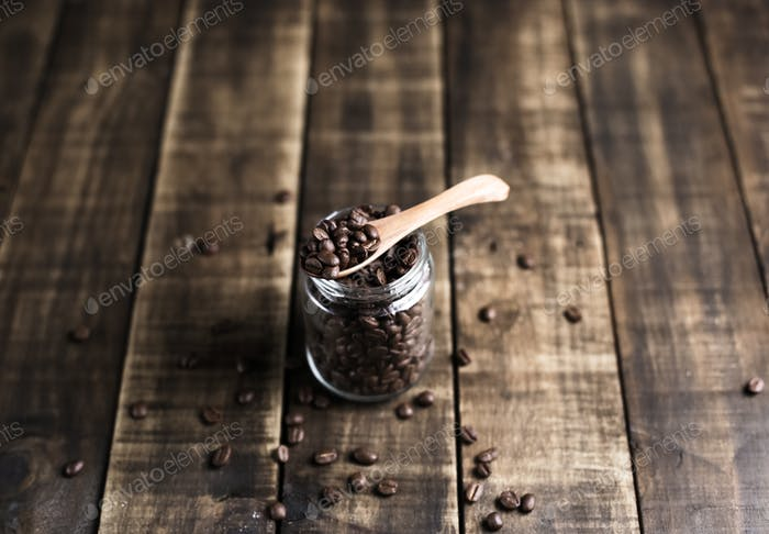 coffee beans in a jug and wooden spoon