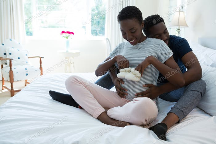 Couple holding baby socks in bedroom