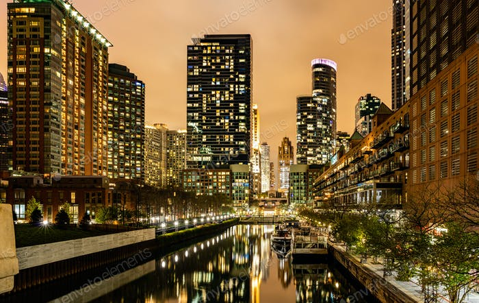 Chicago city illuminated buildings in the evening. Reflections on the river canal