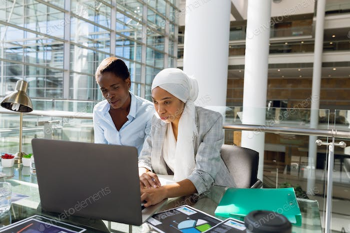 Females executives working together on laptop at desk