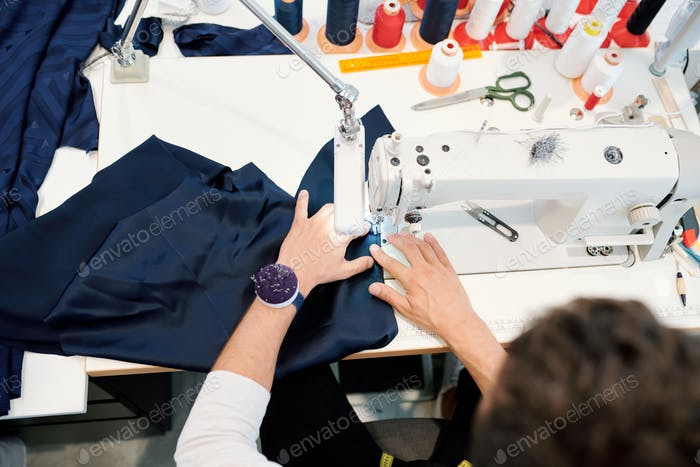 Hands of young man by sewing machine working over one of orders of clients