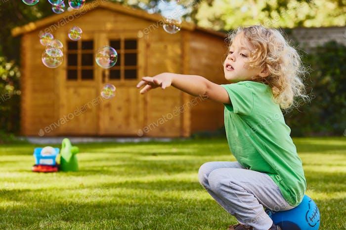 Small boy playing in garden