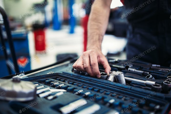 Set of tools for repair in car service - mechanic's hands, close up
