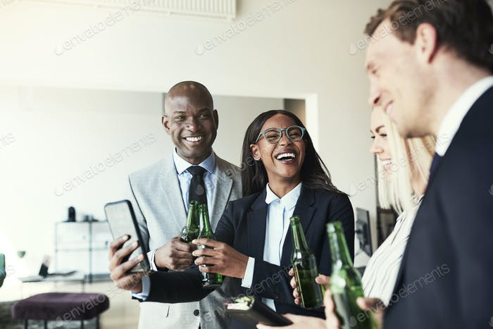 Laughing businesswoman showing coworkers photos over drinks after work
