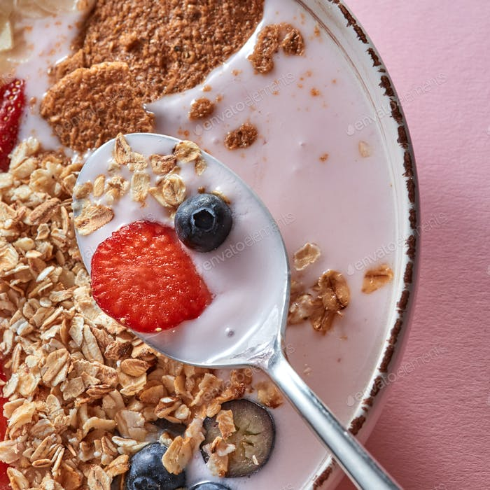 Organic granola with pieces of juicy strawberries, oat flakes, yogurt, almons in a ceramic bowls on