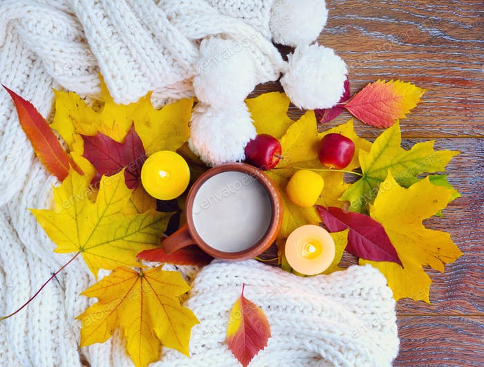 Autumn composition. Cup of coffee, colorful leaves, candles and