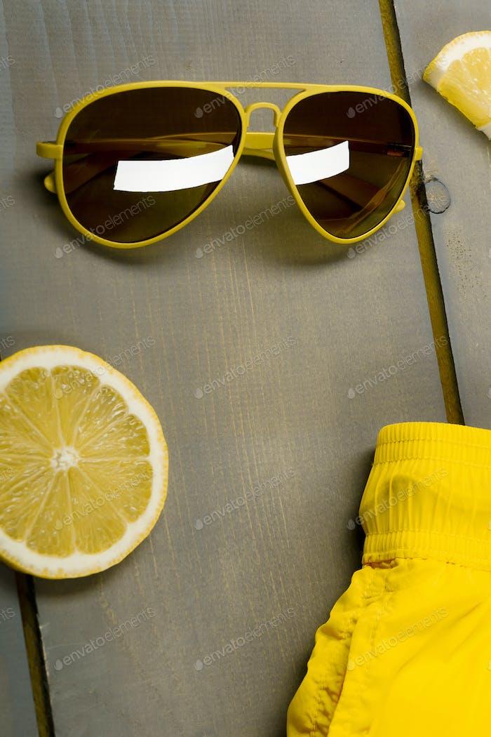Gelbe Piloten-Sonnenbrille nahe Zitrone auf grauem Holzbrett. Strandaccessoires auf hölzernem Hintergrund.