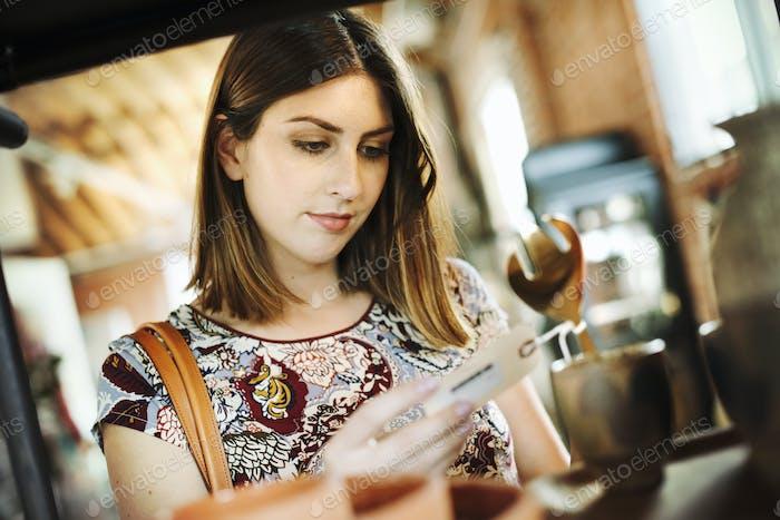 Mujer joven en una tienda, mirando un precio.