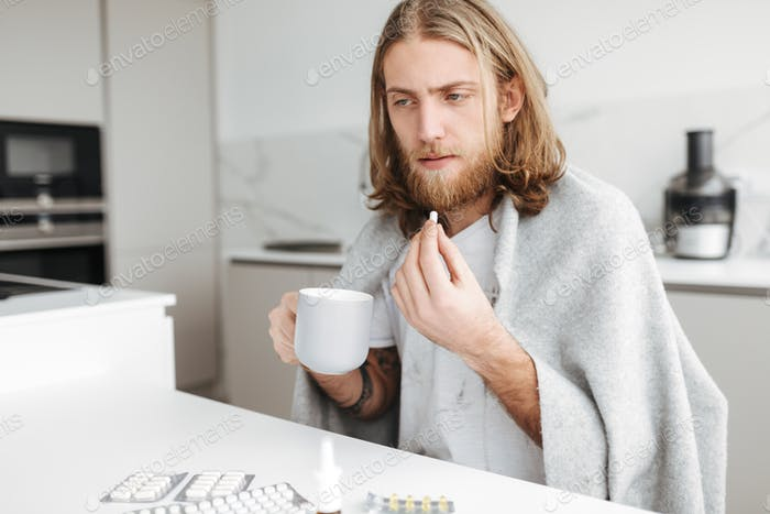 Ill man sitting with mug and pills in hands in kitchen at home