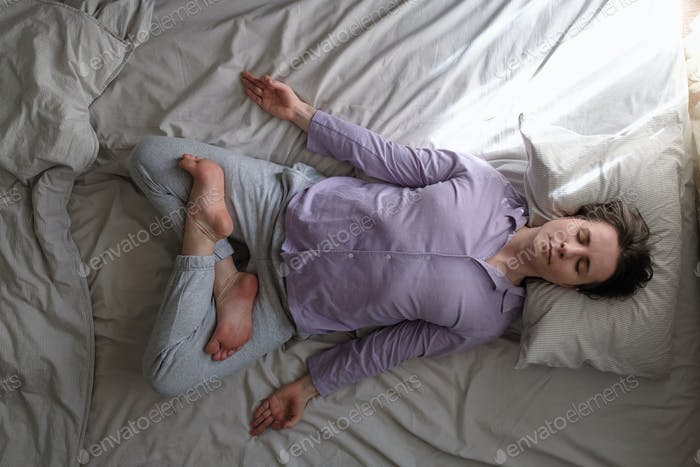 Healthy caucasian woman meditating in lotus position on bed in bedroom.