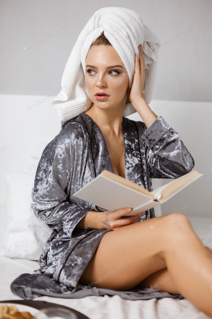 Pretty woman in lingerie and robe in bed with towel on head and book in hands dreamily looking aside