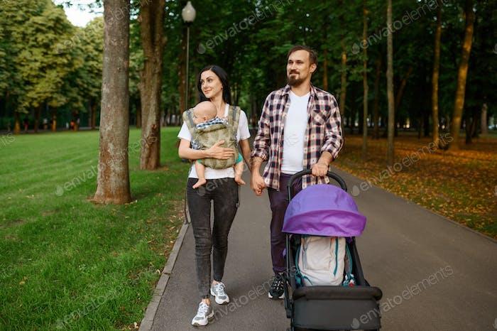 Pais com bebê andando pela calçada no parque