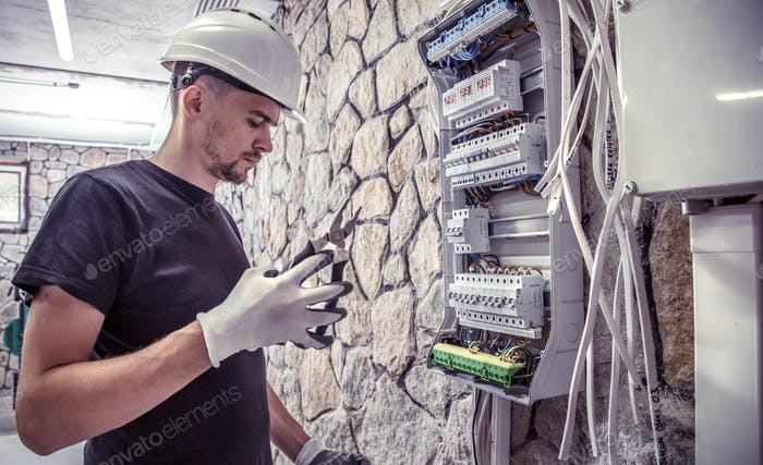 a male electrician works in a switchboard with an electrical connecting cable