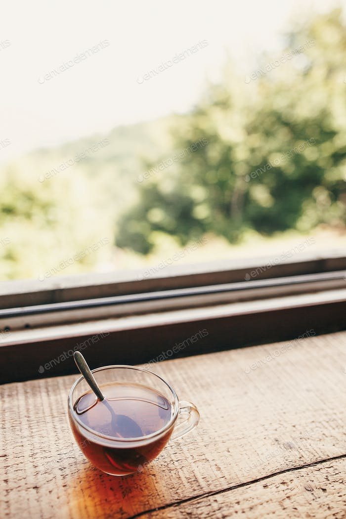 glass of hot tea on wooden table at window light