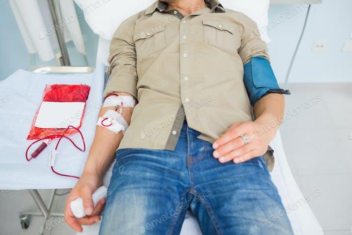 Männlicher Patient, der eine Bluttransfusion in Krankenhausstation erhält