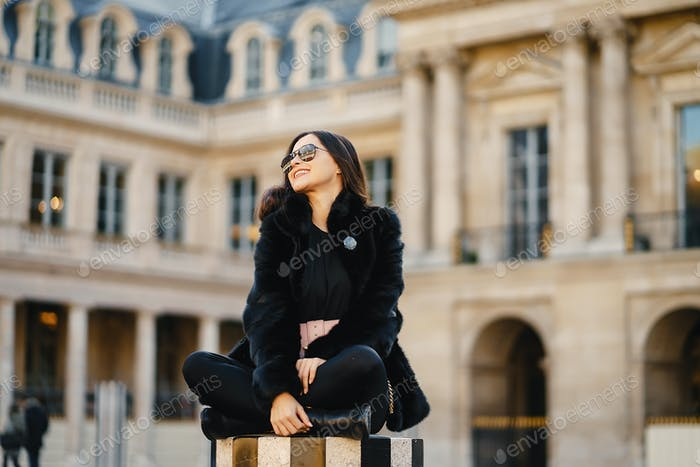 girl sitting at a landmark in paris
